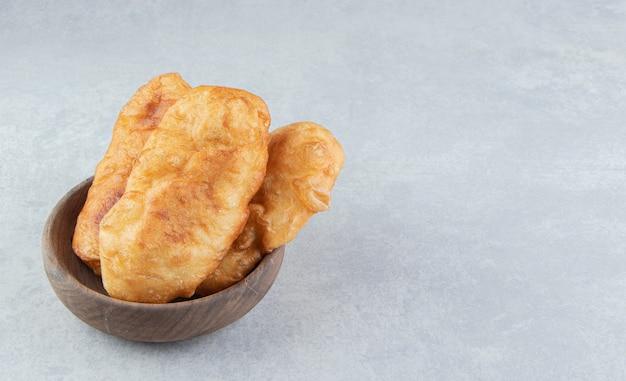 Gebakken piroshki met aardappelen in houten kom.