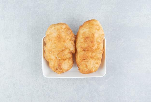 Gebakken piroshki met aardappelen in witte kom.