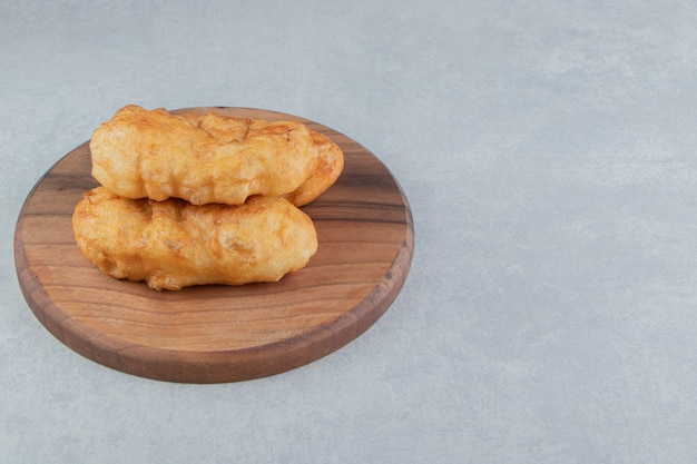 Gebakken piroshki met aardappelen op een houten bord.