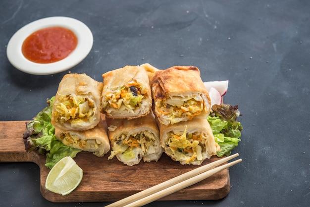 Gebakken plantaardige loempia's met verse ingrediënten geserveerd en zure saus in een oosters restaurant