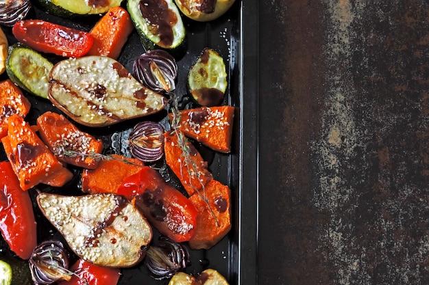 Gebakken pompoen, courgette, paprika, peer, appel, blauwe ui met kruiden en specerijen op een bakplaat. gebakken mix groenten en fruit. veganistische lunch