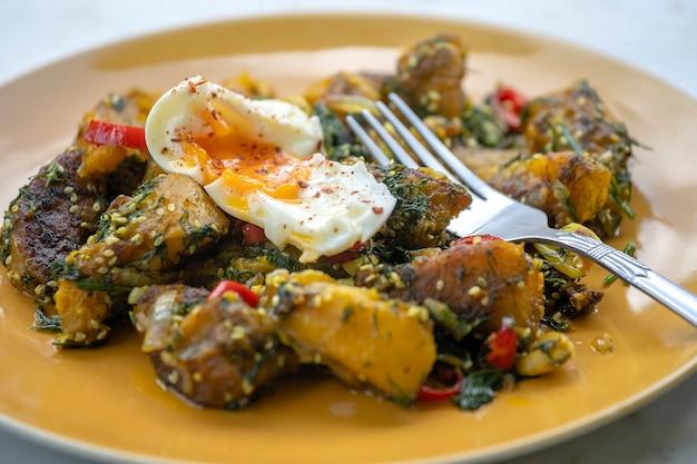 Gebakken pompoen met kruiden samen zachtgekookt ei, bovenaanzicht, close-up