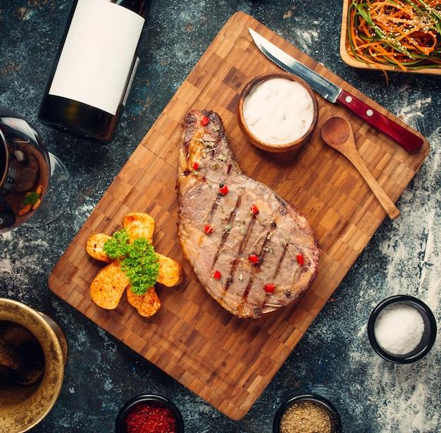 Gebakken rib eye steak op houten bord