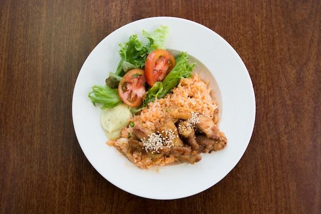 Gebakken rijst kip met aardappel en groente in witte schotel op houten tafel. aziatische gebakken rijst nasi goreng met kip.