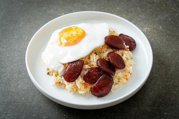Gebakken rijst met gebakken ei en chinese worst - huisgemaakt eten in aziatische stijl