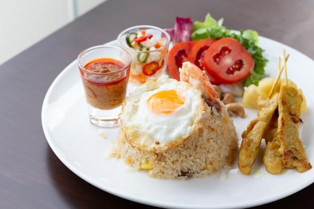 Gebakken rijst met gebakken ei met geroosterd varkensvlees en salade