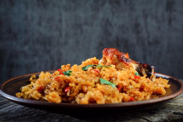 Gebakken rijst met groenten en gebakken kip op een houten tafel