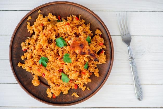 Gebakken rijst met groenten en kip in saus in een bord op een witte tafel
