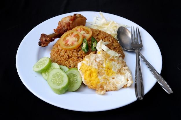 Gebakken rijst met kip, eieren, groenten geïsoleerd op zwarte achtergrond