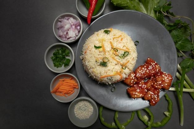 Gebakken rijst met kip en groente op donkere plaat en donkere achtergrond