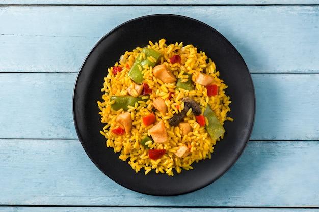 Gebakken rijst met kip en groenten in zwarte plaat op blauwe houten tafel bovenaanzicht
