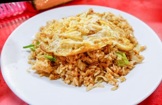 Gebakken rijst met omelet bovenop op witte plaat