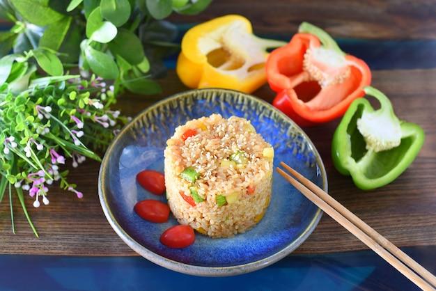 Gebakken rijst met paprika en courgette gegarneerd met kerstomaatjes