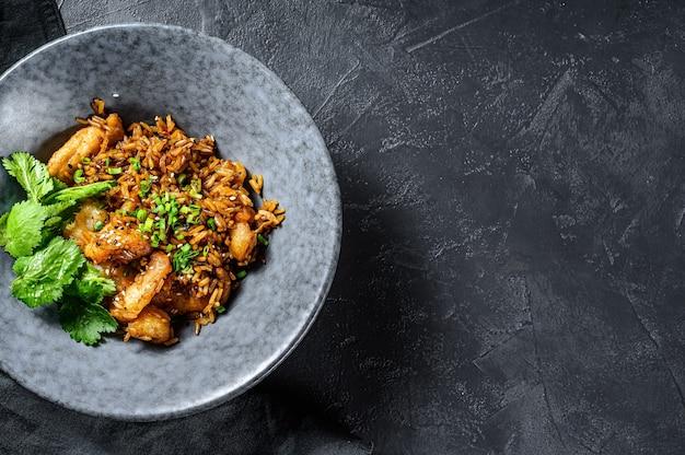 Gebakken rijst met pikante saus en garnalen, garnalen. zwarte achtergrond