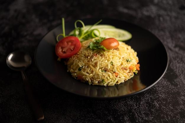 Gebakken rijst met varkensgehakt, tomaat, wortel en komkommer op het bord