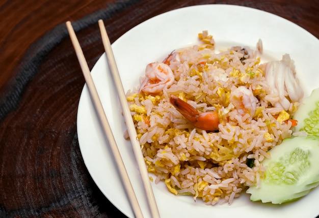 Gebakken rijst met zeevruchten en gesneden komkommer