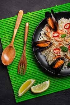 Gebakken rijst met zeevruchten mosselen, garnalen, basilicum in een zwarte plaat met houten lepel en vork op groene bamboe mat en stenen tafel. bovenaanzicht.