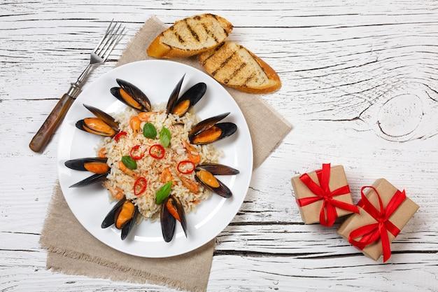 Gebakken rijst met zeevruchten mosselen, garnalen en basilicum in een bord met jute, geroosterd stokbrood en geschenkdozen op witte gebarsten houten tafel. bovenaanzicht.