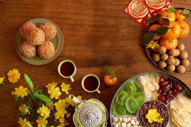 Gebakken rijstballen, heerlijke gedroogde vruchten en noten op tafel versierd met abrikozenbloemen en wenskaarten met de beste wensen inscriptie voor maannieuwjaar
