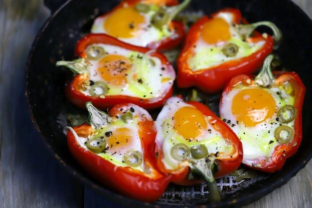 Gebakken rode paprika met ei in een koekenpan.