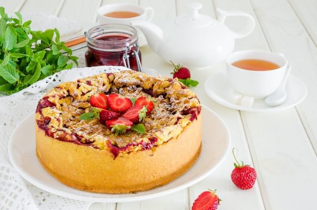 Gebakken romige cheesecake met aardbeien en knapperige shtrezel op een plaat op een witte houten achtergrond met een kopje thee.