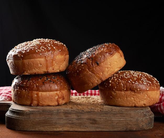 Gebakken ronde knapperige sesambroodjes voor hamburgers op bruin houten bord