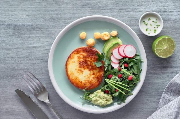 Gebakken ronde plak kaas met groene rucolasalade met avocado, radijs en granaatappelzaden, geserveerd met yoghurtsaus. plat op neutrale textuur.