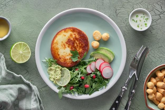 Gebakken ronde plak kaas met groene rucolasalade met avocado, radijs en granaatappelzaden, geserveerd met yoghurtsaus