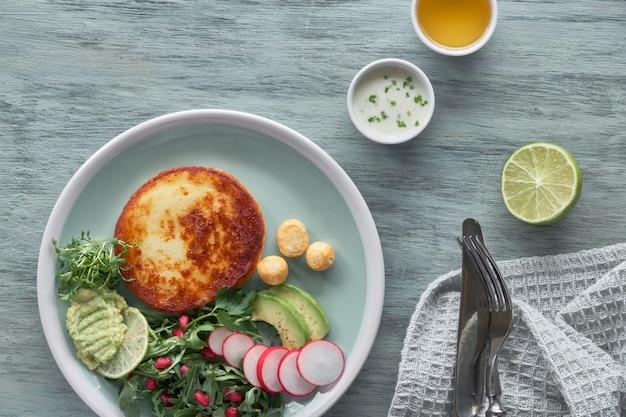 Gebakken ronde plak kaas met groene rucolasalade met avocadoradijs en granaatappelzaden, geserveerd met yoghurtsaus