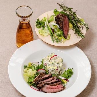 Gebakken rundvlees op een bord met ingrediënten voor okroshka-kruiden en een karaf kvass