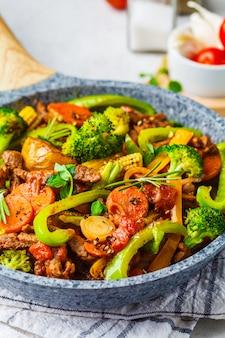 Gebakken rundvlees stroganoff met aardappelen en groenten in een pan.