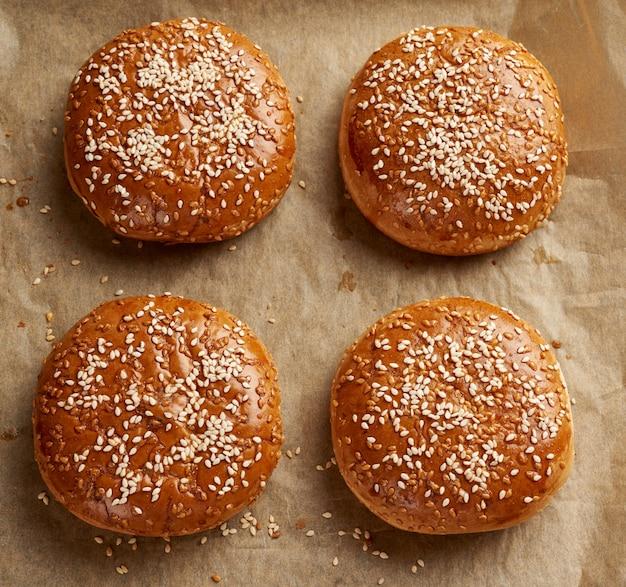 Gebakken sesambroodjes op bruin perkamentpapier, ingrediënt voor een hamburger, bovenaanzicht
