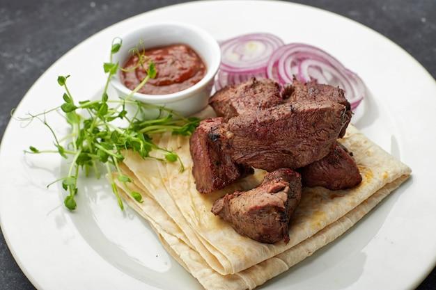 Gebakken shish kebab met lavash, saus, microgreen en ui op een witte plaat op grijs