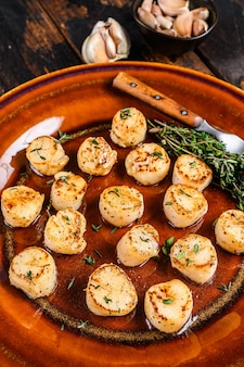 Gebakken sint-jakobsschelpen met boter pikante saus in een bord.