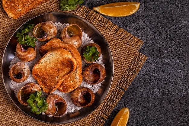 Gebakken slakken met citroen, stokbrood en peterselie