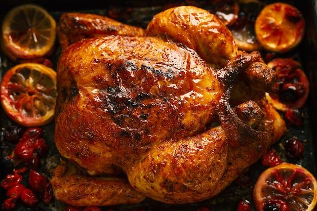Gebakken smakelijke hele kip met sinaasappels en veenbessen in ovenvorm. detailopname