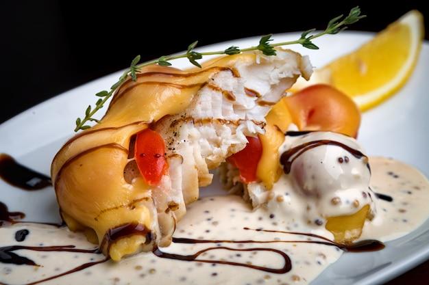 Gebakken snoekbaars visfilet gesneden, met kaas, met witte saus, plakjes tomaat en een takje rozemarijn, op een witte plaat, op zwart