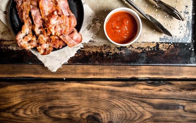 Gebakken spek in een koekenpan en tomatensaus. op een houten tafel.