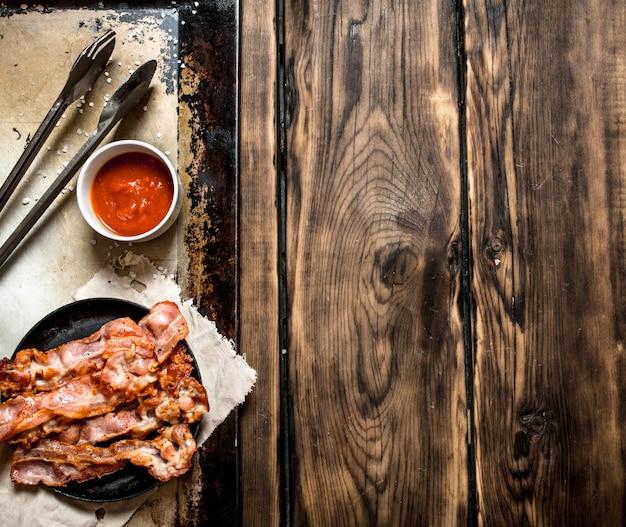 Gebakken spek in een koekenpan en tomatensaus. op een houten tafel. Premium Foto