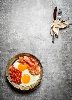 Gebakken spek met eieren en bonen in de pan mes en vork in de oude stof op de stenen tafel