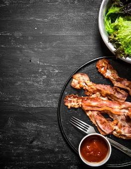 Gebakken spek met saus en groenten. op een zwarte houten achtergrond.