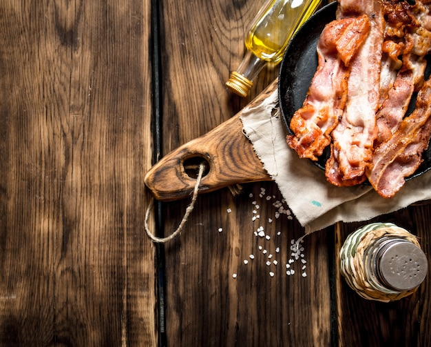 Gebakken spek met zout in een koekenpan op het bord. op een houten tafel.