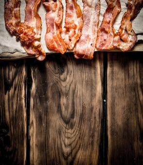 Gebakken spek op de stof. op een houten tafel. Premium Foto