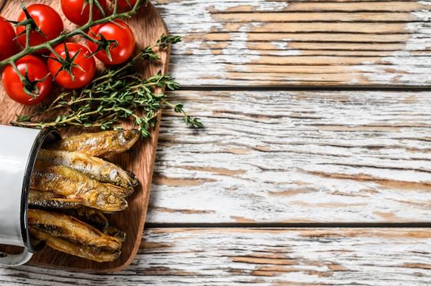 Gebakken spiering in de pan op tafel met tomaten en peper. witte achtergrond. bovenaanzicht. kopieer ruimte