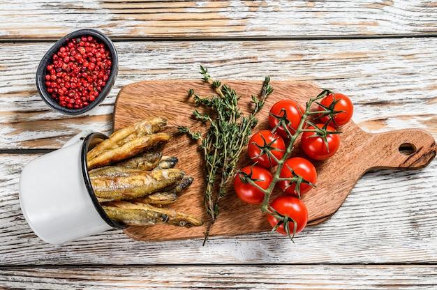 Gebakken spiering in de pan op tafel met tomaten en peper. witte achtergrond. bovenaanzicht