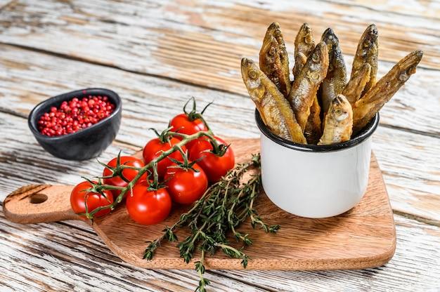 Gebakken spiering in de pan op tafel met tomaten en peper