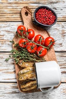 Gebakken spiering in de pan op tafel met tomaten