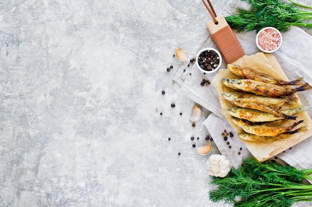 Gebakken spiering op een houten snijplank, dille, roze zout, peper en knoflook.