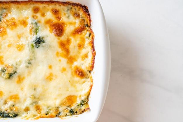 Gebakken spinazie lasagne met kaas in witte plaat