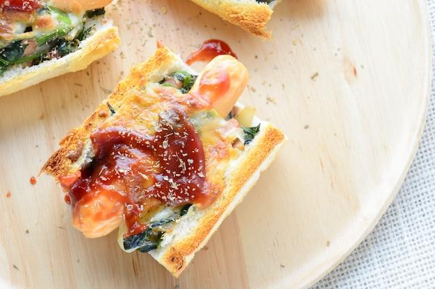 Gebakken spinazie met kaas, worst op stokbrood, stokbrood